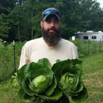 Zac with our first cabbage harvest.